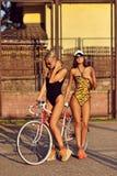 Härliga sexiga kvinnor i baddräkter som poserar nära en tappning, cyklar Royaltyfri Fotografi