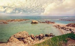Härliga sikter av havet och den steniga kusten av Cypern med en molnig himmel på en solig dag Horisontalramen Arkivbilder
