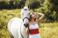 Härliga sinnliga kvinnor med den vita hästen Arkivfoto