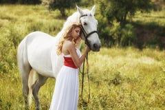 Härliga sinnliga kvinnor med den vita hästen Arkivfoton