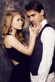 Härliga sinnliga par i elegant kläder som poserar i studio Fotografering för Bildbyråer