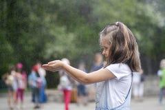 Härliga små behandla som ett barn öppnande händer för flickan med vattensprej royaltyfria foton