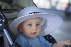 Härliga små behandla som ett barn med blåa ögon i en vit hatt Royaltyfri Foto
