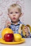 Härliga små behandla som ett barn pojken äter bananen arkivbild