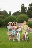 Härliga små flickor som rider en cykel till och med parkera Natur livsstil Royaltyfri Bild