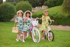 Härliga små flickor som rider en cykel till och med parkera Natur livsstil Arkivfoto