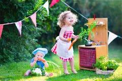 Härliga små ungar som spelar med leksakkök i trädgården arkivfoto