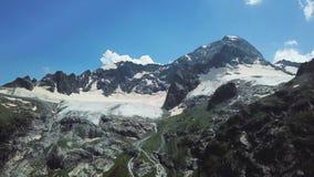 Härliga snö-korkade berg mot den blåa himlen Bästa sikt av överkanten av berget med snölocket stock video