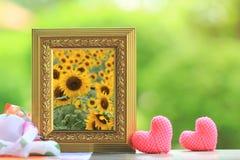 Härliga solrosor som blommar i guld- ram med hjärta på tabellen fotografering för bildbyråer