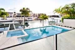 Härliga solstrålar som faller på simbassäng i det lyxiga huset royaltyfri foto