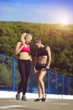 Härliga sportflickor poserar på en trampkvarn Fotografering för Bildbyråer