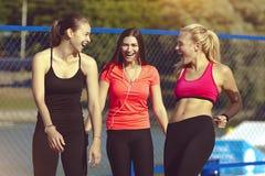Härliga sportflickor skrattar, når sportde har utbildat Sunda unga kvinnor leder en lycklig och sund livsstil Fotografering för Bildbyråer
