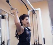 Härliga sportiga flickabygganden tränga sig in armar och bröstkorgen i idrottshallen Arkivfoto