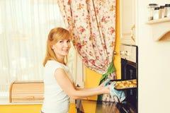 Härliga stekheta kakor för ung kvinna i ugn på kök Royaltyfria Bilder