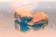 Härliga stenar på en reflekterande yttersida Arkivfoto