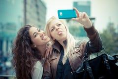 Härliga stilfulla unga kvinnor för blondin och för brunett Arkivfoton