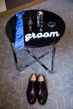 Härliga svarta läderskor och annan tillbehör av brudgummen på den svarta tabellen Royaltyfri Bild