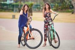 Härliga systrar som tillsammans utomhus poserar på deras färgglade cyklar royaltyfri fotografi
