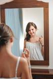 Härliga teen studier för en flicka henne, utseendemässig som hon ser in i avspegla Arkivfoton