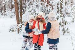 Härliga tonårs- flickor som har den roliga yttersidan i ett trä med insnöad vinter Kamratskap och aktivt livbegrepp fotografering för bildbyråer