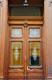 Härliga trädörrar för antikvitetdubblettingång med glass rektanglar med vit målade blom- prydnader Arkivbild