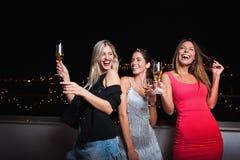 Härliga tre, gladlynta kvinnor som har en flickanatt ut och att ha gyckel arkivbild