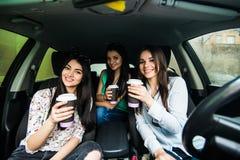 Härliga tre kvinnor är sitta och köra en bil som rymmer en mobiltelefon och en messaging Tre flickor som dricker kaffe och ser f royaltyfri bild