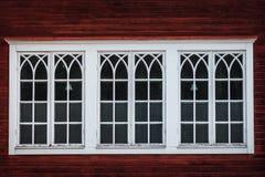 Härliga trefaldiga vita fönster på en röd träbyggnad Royaltyfri Bild