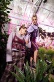 Härliga trevliga modeller som är i en blommaträdgård royaltyfria foton