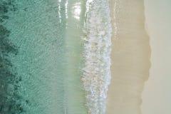 Härliga tropiska vita tömmer stranden, och havet vinkar sett från över Flyg- sikt för Seychellerna strand royaltyfri fotografi