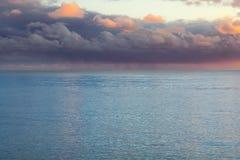 Härliga tunga purpurfärgade moln över havet fotografering för bildbyråer