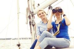 Härliga två, attraktiva unga flickor med binokulärt på en yacht royaltyfri fotografi