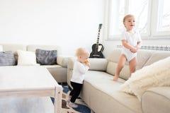 Härliga två behandla som ett barn att spela i vardagsrummet isolerad systerwhite för bakgrund broder Royaltyfria Bilder