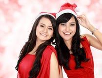 Härliga två flickor i den julsanta hatten har gyckel Arkivfoto