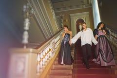 Härliga två kvinnor och en man i kläderen av den 18th centuren Royaltyfria Foton