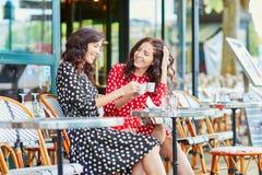 Härliga tvilling- systrar som dricker kaffe Royaltyfri Foto