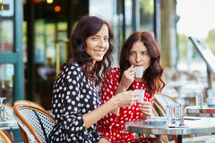 Härliga tvilling- systrar som dricker kaffe Fotografering för Bildbyråer