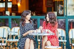 Härliga tvilling- systrar som dricker kaffe Arkivfoton
