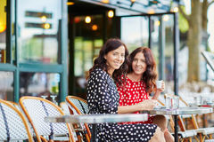 Härliga tvilling- systrar som dricker kaffe Arkivbild