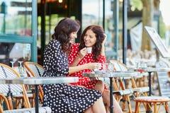 Härliga tvilling- systrar som dricker kaffe Arkivfoto