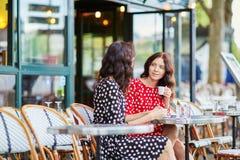 Härliga tvilling- systrar som dricker kaffe Arkivbilder