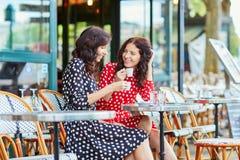 Härliga tvilling- systrar som dricker kaffe i Paris Fotografering för Bildbyråer