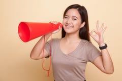 Härliga unga asiatiska den reko kvinnashowen meddelar med megafonen Arkivbild