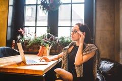 Härliga unga bärande exponeringsglas för brunettaffärskvinna och tröjabruksbärbar dator som skrivar ut text på tangentbordet I ka Royaltyfria Foton
