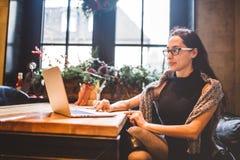 Härliga unga bärande exponeringsglas för brunettaffärskvinna och tröjabruksbärbar dator som skrivar ut text på tangentbordet I ka Arkivfoto