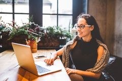 Härliga unga bärande exponeringsglas för brunettaffärskvinna och tröjabruksbärbar dator som skrivar ut text på tangentbordet I ka Arkivfoton
