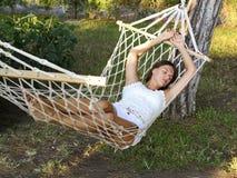 Härliga unga brunettkvinnalögner i en hängmatta som tycker om, vilar a Arkivbild
