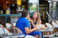 Härliga unga datummärkningpar i parisiskt kafé Royaltyfri Bild