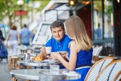 Härliga unga datummärkningpar i parisiskt kafé Arkivbilder
