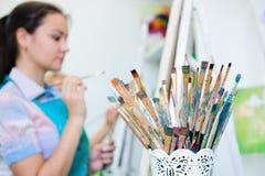 Härliga unga flickor drar en bild målar på konstkurs arkivfoto
